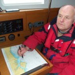 photo of man sitting at yacht chart table