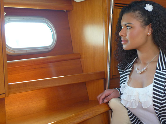 girl looks out of boat porthole